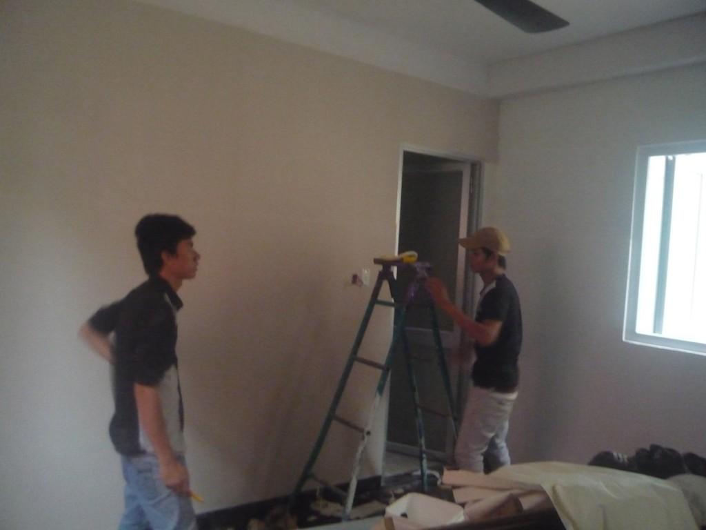 nhân viên đang thi công dán giấy dán tường